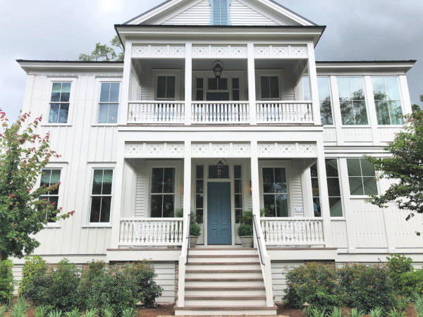White farmhouse with blue shutters and trim