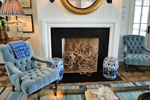 Coastal home fireplace with branches in the fireplace and blue chairs flanking the fireplace