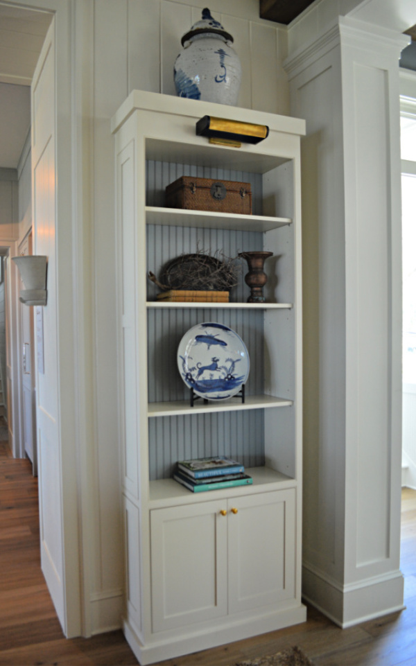 White bookshelf backed with blue bead board with blue and white accessories