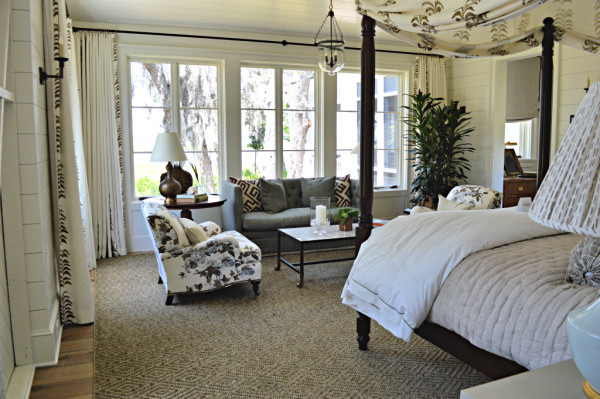 A master bedroom with neutral decor and accents of blue looks toward the inter coastal waterway through trees draped with Spanish moss.