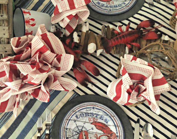 Overhead picture of a lobster themed dinner party place settings with plastic lobsters