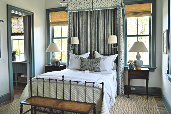 A southern bedroom with a faux canopy is ready to welcome guests with blue accents and matchstick blinds.