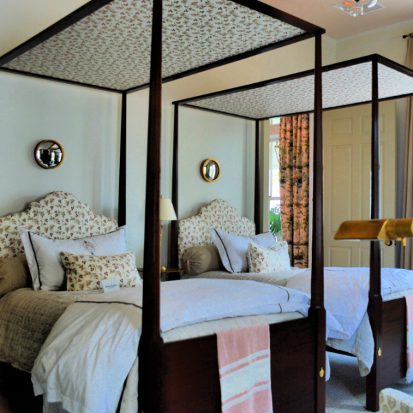 A pair of four poster beds with upholstered headboards grace an elegant bedroom
