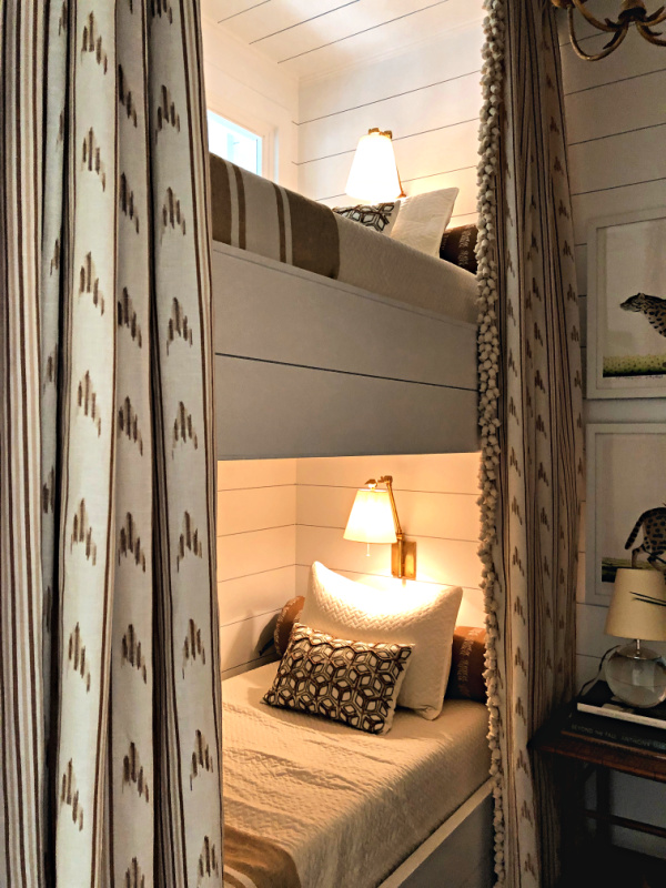 A dressy elegant bunk room has neutral color curtains with heavy fringe