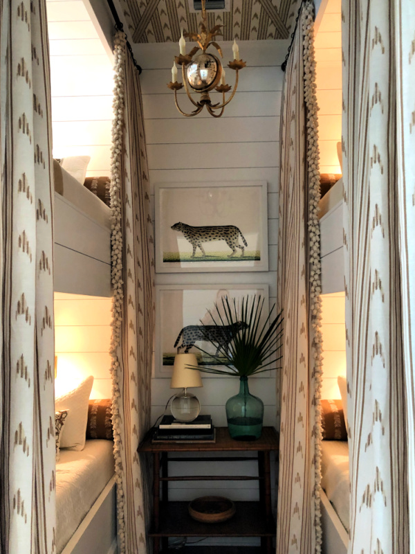 A tiny bunk room is elegant with british colonial accents and a brass chandelier