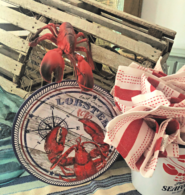 Vintage looking melamine dinner plates with a lobster on them and a lobster trap