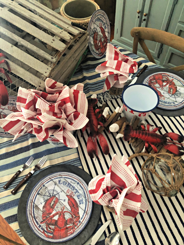 Table set for a seafood party with lots of lobster and coastal accents
