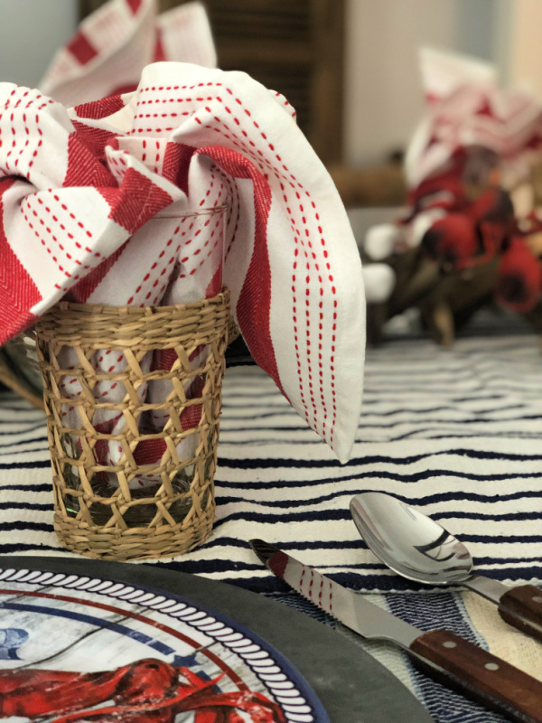 Glass wrapped in seagrass or rattan holder with a red and white cloth napkin tucked inside