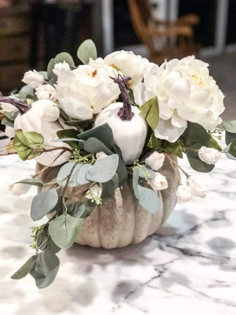 Rustic colored pumpkin with a white flower and eucalyptus floral arrangement in the pumpkin and a couple of white faux pumpkins in the arrangement