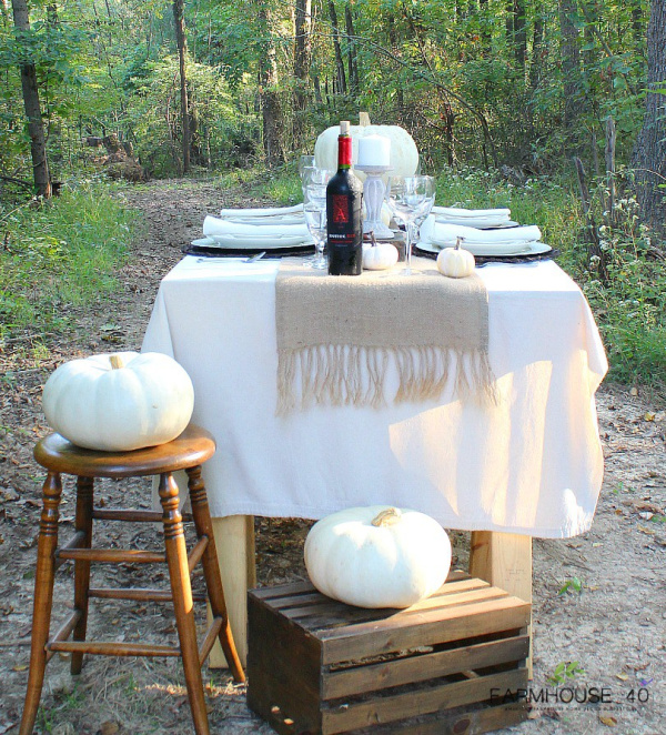 beautiful table set in the out of doors with a crisp white tablecloth, a burlap table runner, adorned with white pumpkins and a bottle of red wine