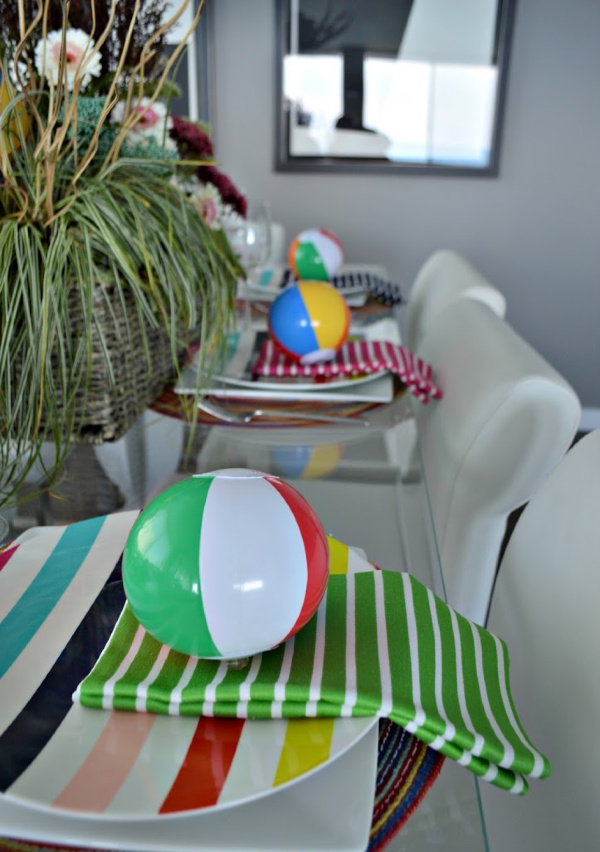 Table set with colorful striped plates and napkins and cute little beach balls