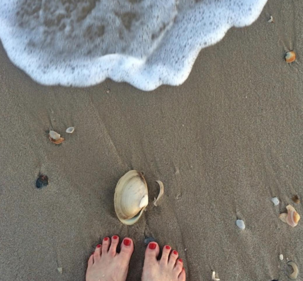 toes in the sand with the wave coming in and seashells on the sand
