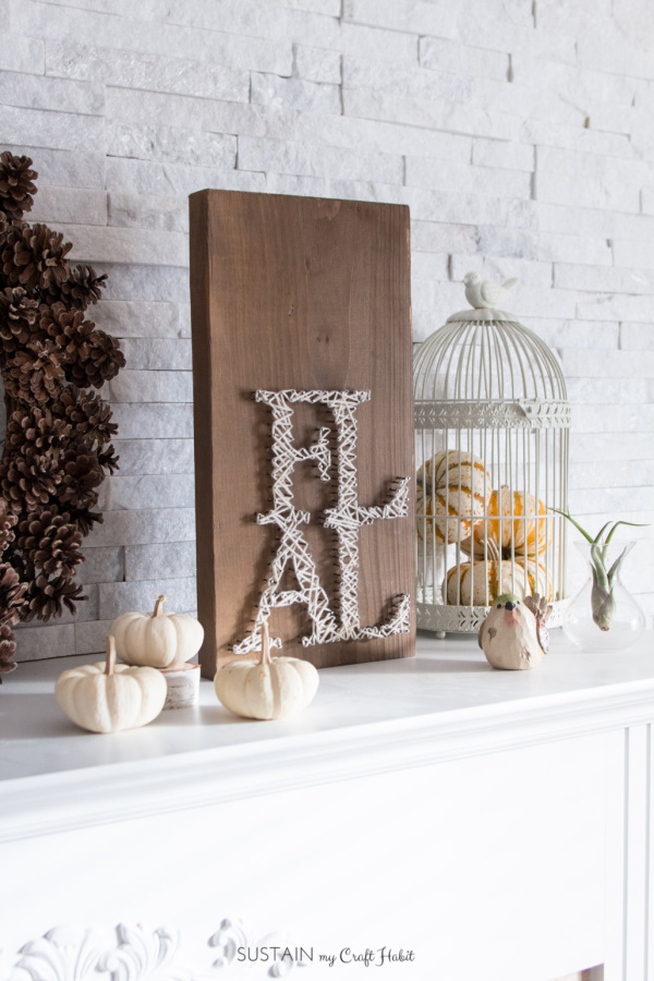 neutral fall vignette with white pumpkins, a white birdcage filled with pumpkins a white brick wall a pinecone wreath and a FALL string art craft project