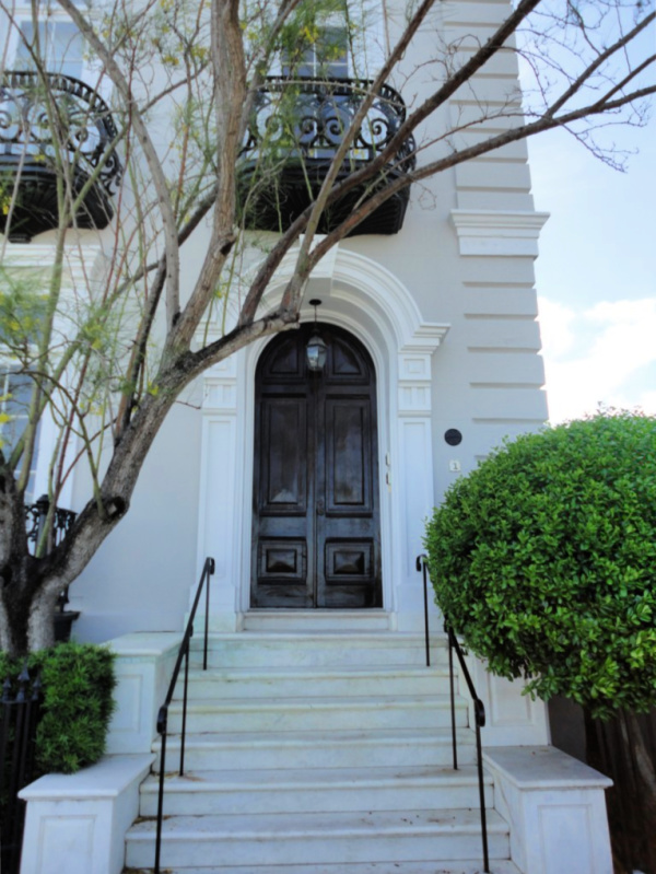 Elegant Charleston home with steps up to the front door with a dark wood arched front door.
