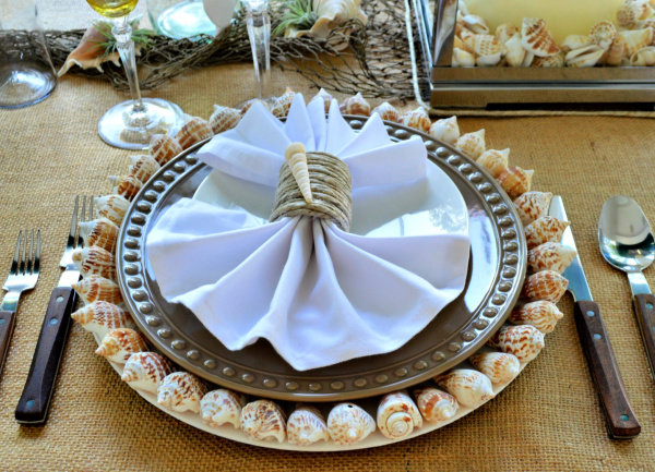 Seaside place setting with neutral colors and seashell chargers and seashell napkin rings