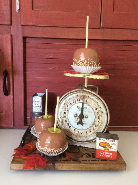 Caramel apples on display on a vintage kitchen scale.