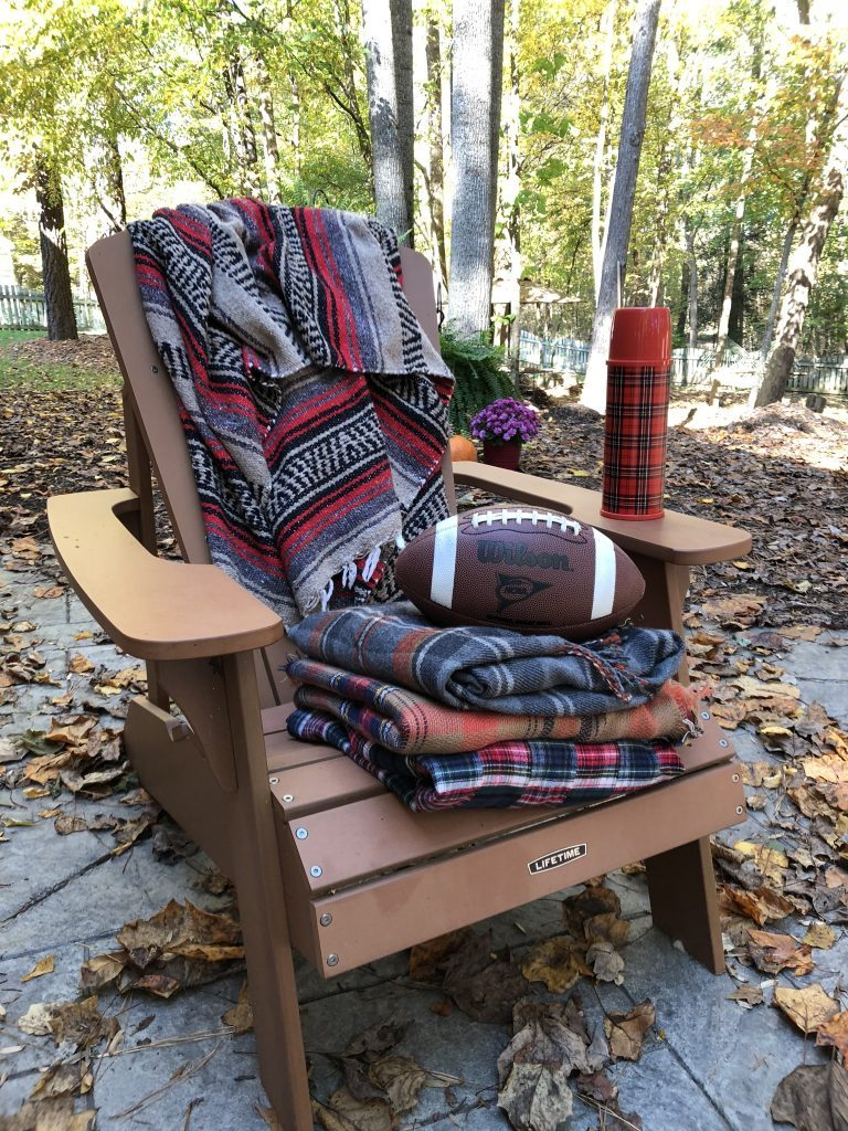 Adirondack chair with fall blankets and a football ready to get cozy for Fall