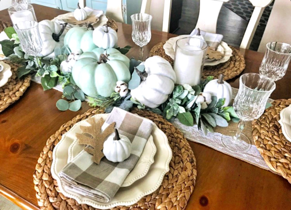 pretty wood dining table set with seagrass placemats and topped with Pioneer woman ivory dinner plates and topped with a neutral buffalo plaid napkin and white pumpkin and a paper oak leaf with a centerpiece of green and white pumpkins, white candles and greenery