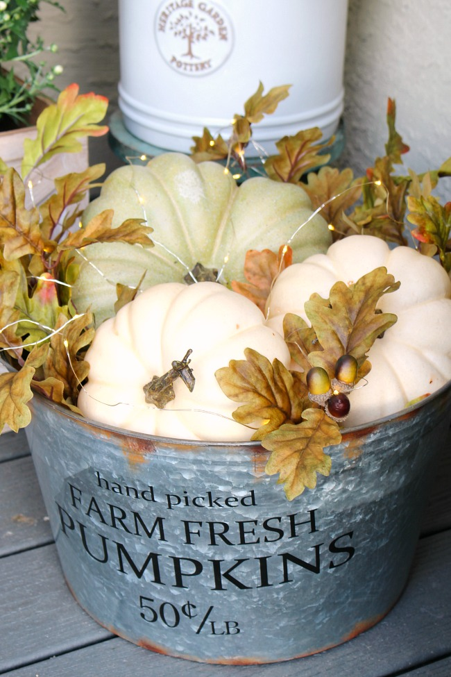 Galvanized pail with Farm Fresh Pumpkins lettering on it filled with white pumpkins and fall leaves with acorns and tiny lights