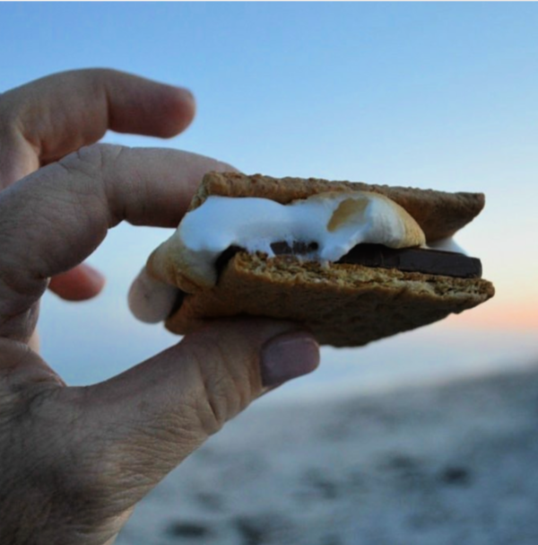 fingers holding a s'mores with the sunset in the background