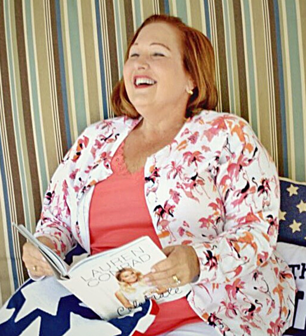 woman sitting on chaise lounge reading a book and laughing