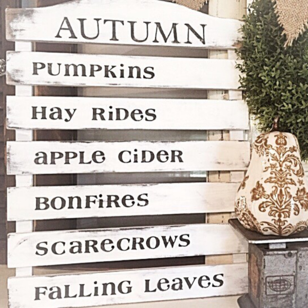Autumn country sign with pumpkins, hay rides, apple cider, bonfires, scarecrows, falling leaves and a white pumpkin with henna on it