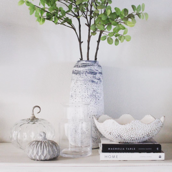 a neutral or white fall vignette with glass crystal pumpkin, white vases and a gray wooden pumpkin and a white bowl on a magnolia table book
