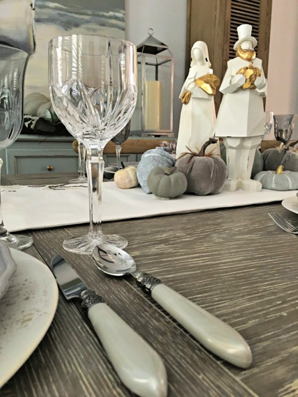 thanksgiving tablescape with gray flatware gray pumpkins, waterford goblets and a pair of modern white pilgrims with gold accents