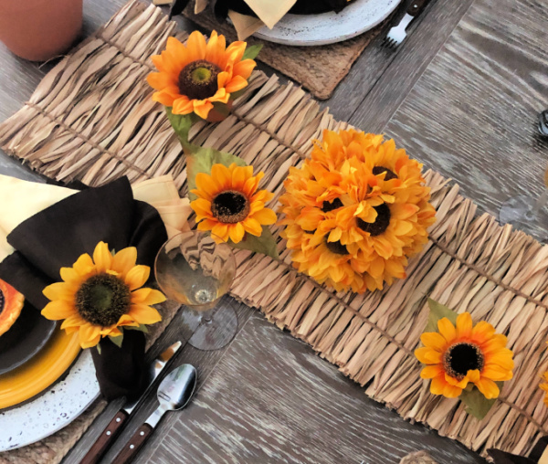 Overhead shot of how to style a table for late summer with sunflower decorations
