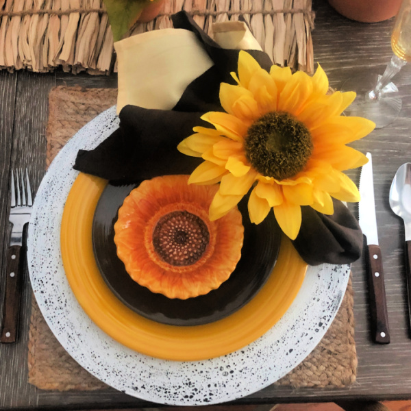 A sunflower table setting with yellow and brown plates and sunflower napkin rings