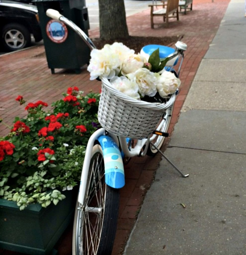 Blue bicycle with white flowers in the basket