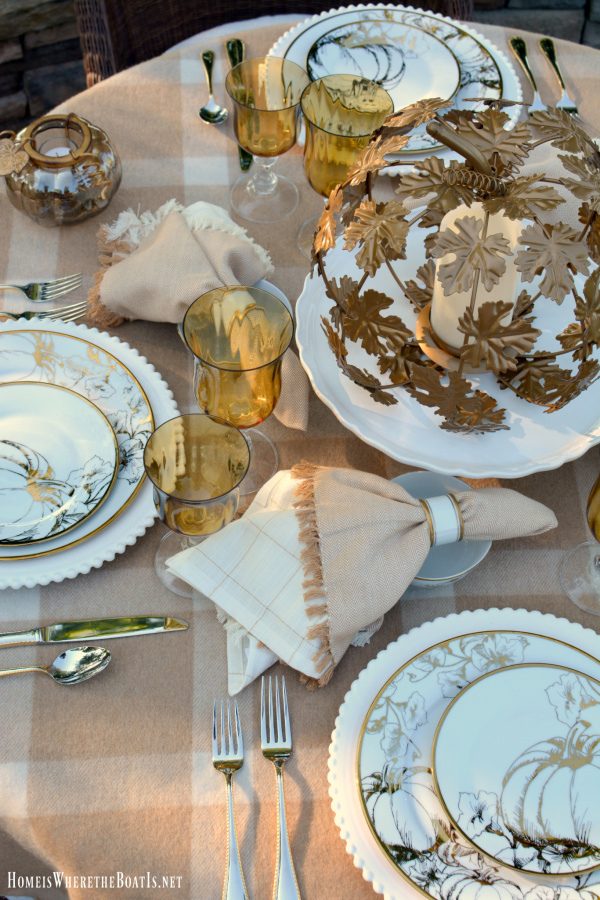 fall table with a gold metal cut leaf pumpkin candle holder as the centerpiece gold pumpkin china and a beige throw over the table