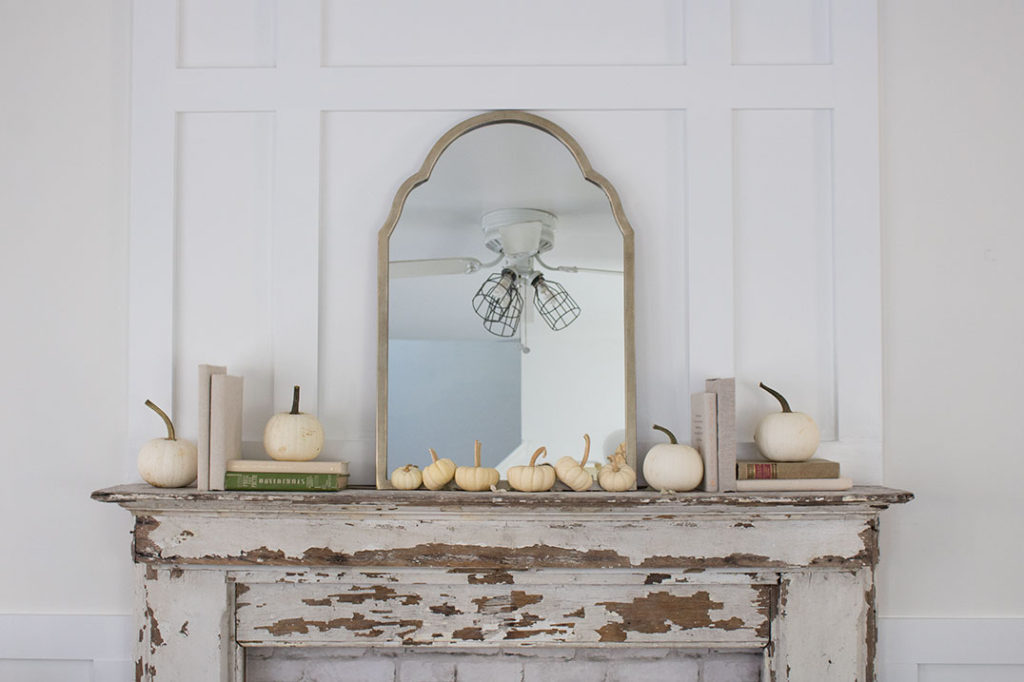 simple chippy mantel piece on a board and batten wall with a farmhouse simple arrangement of books and tiny white pumpkins with a mirror as the centerpiece