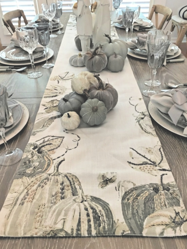 fall or thanksgiving table with elegant gray and white table runner and gray and white pumpkins and gray crystal goblets