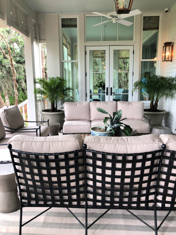 Beautiful back porch with comfy furniture and palms in pots