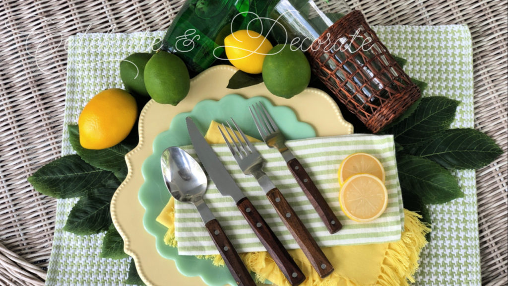 A lemon lime tablescape with yellow Nicole Miller scalloped dinner plates, Pioneer woman jade green salad plates and Ikea wood handled flatware and green and white striped napkins