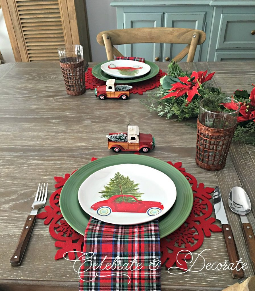 Christmas tablescape with little red trucks with Christmas trees in the back of the trucks
