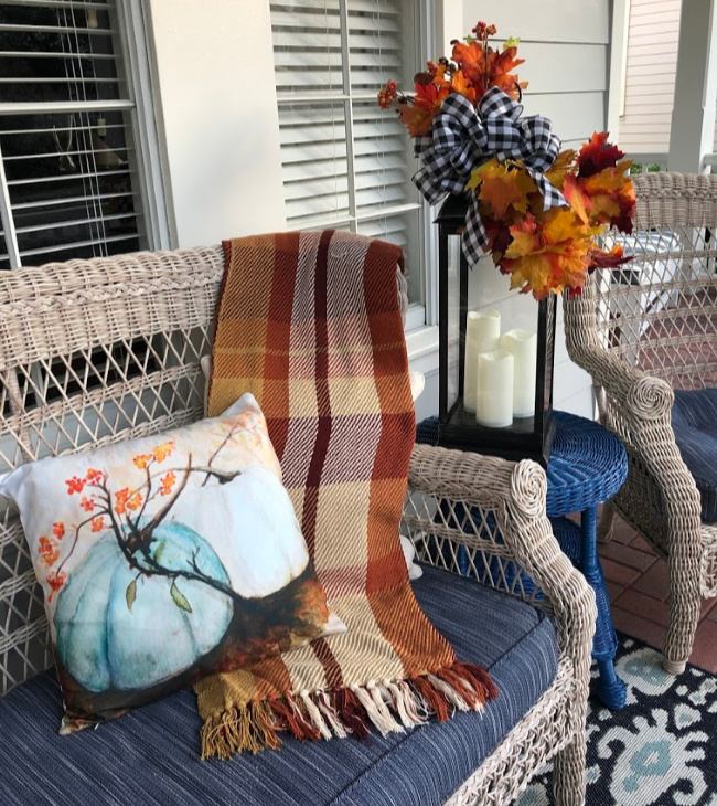 wicker settee on front porch with fall pillow and plaid fall throw