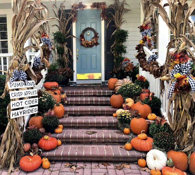 Front porch with brick steps decorated for fall with cornstalks, pumpkins and mums