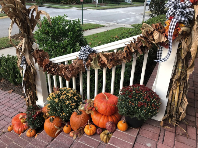 Brick steps pumpkins and mums and fall leaves garland