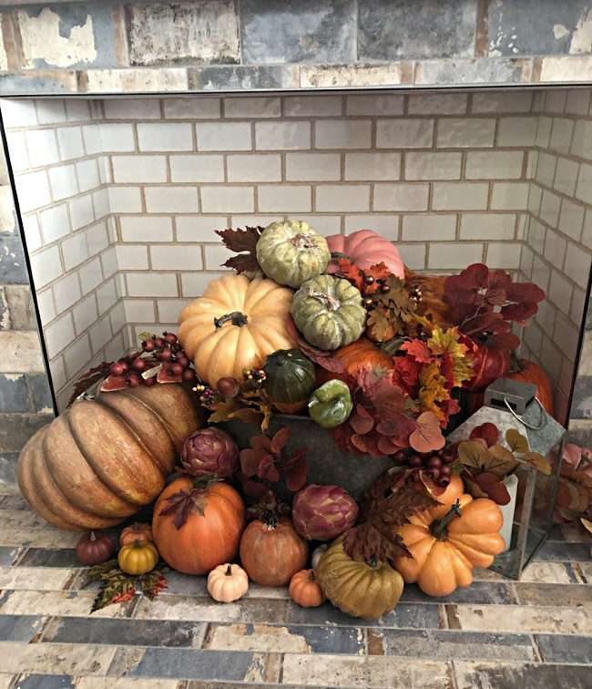 Hearth filled with and array of pumpkins and gourds and fall leaves for fall