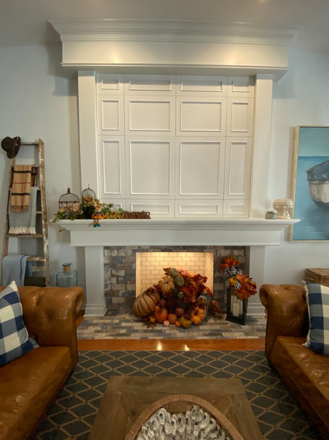Living room decorated for thanksgiving or fall with white paneled fireplace and leather chesterfield sofas