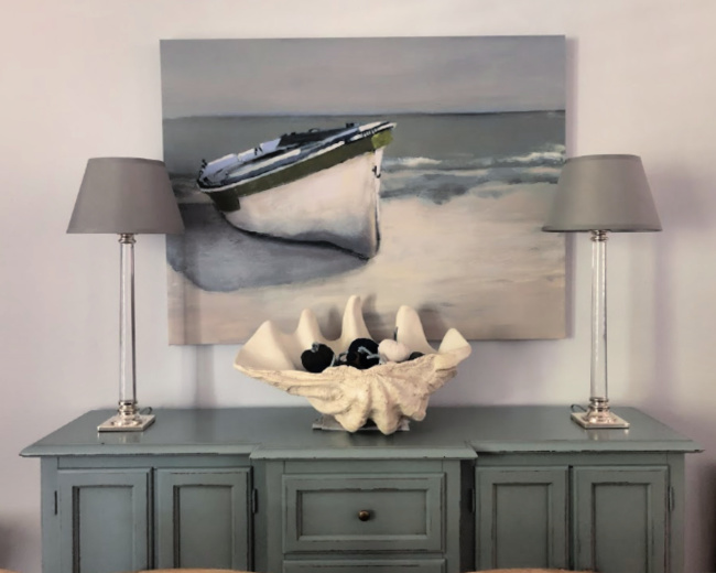 Blue sideboard with a painting of a boat above it, candlestick lamps on it and a giant clamshell filled with blue and gray pumpkins