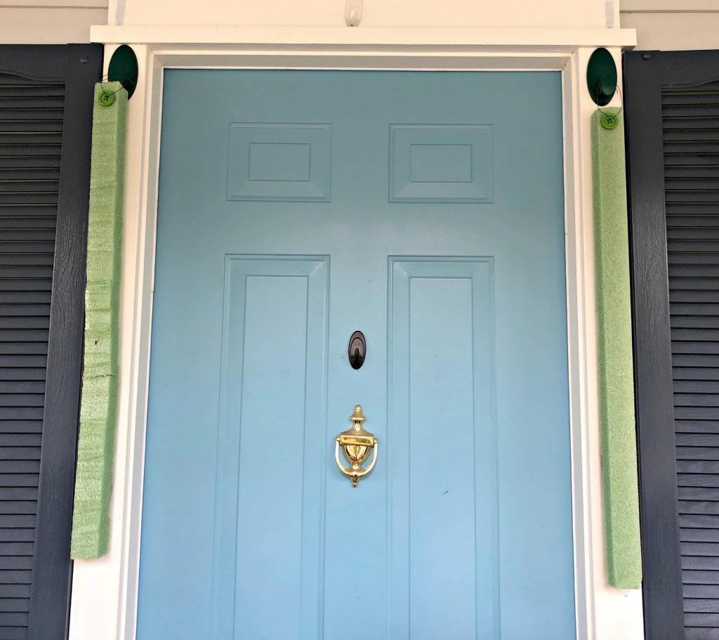 Strips of styrofoam hung next to a blue front door.
