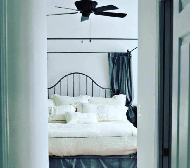 Pretty neutral bedroom with cream and gray colored linens on a campaign bed