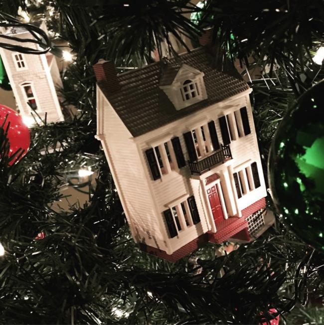 Hallmark victorian house christmas ornament on a christmas tree.