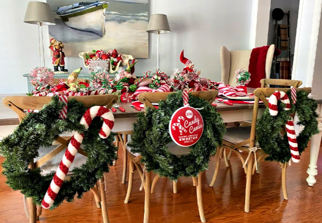The back of chairs decorated with candy canes and wreaths for a holiday table.