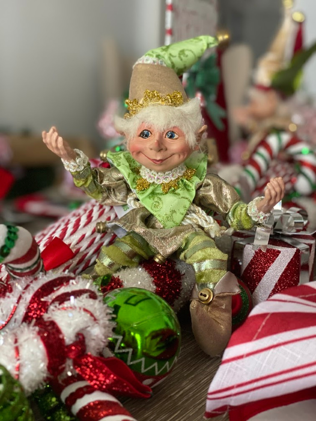 A cute little christmas elf as part of a centerpiece for a holiday table.