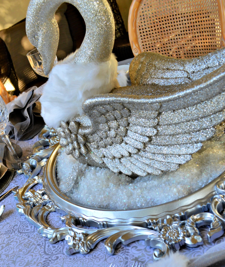 Silver glitter swan wearing a white fur stole swimming on a lake of glistening snow in an ornate silver frame