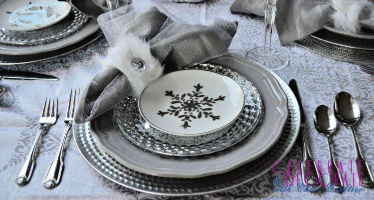 Gray, white and silver dishes with silver flatware adorn a winter tablesetting
